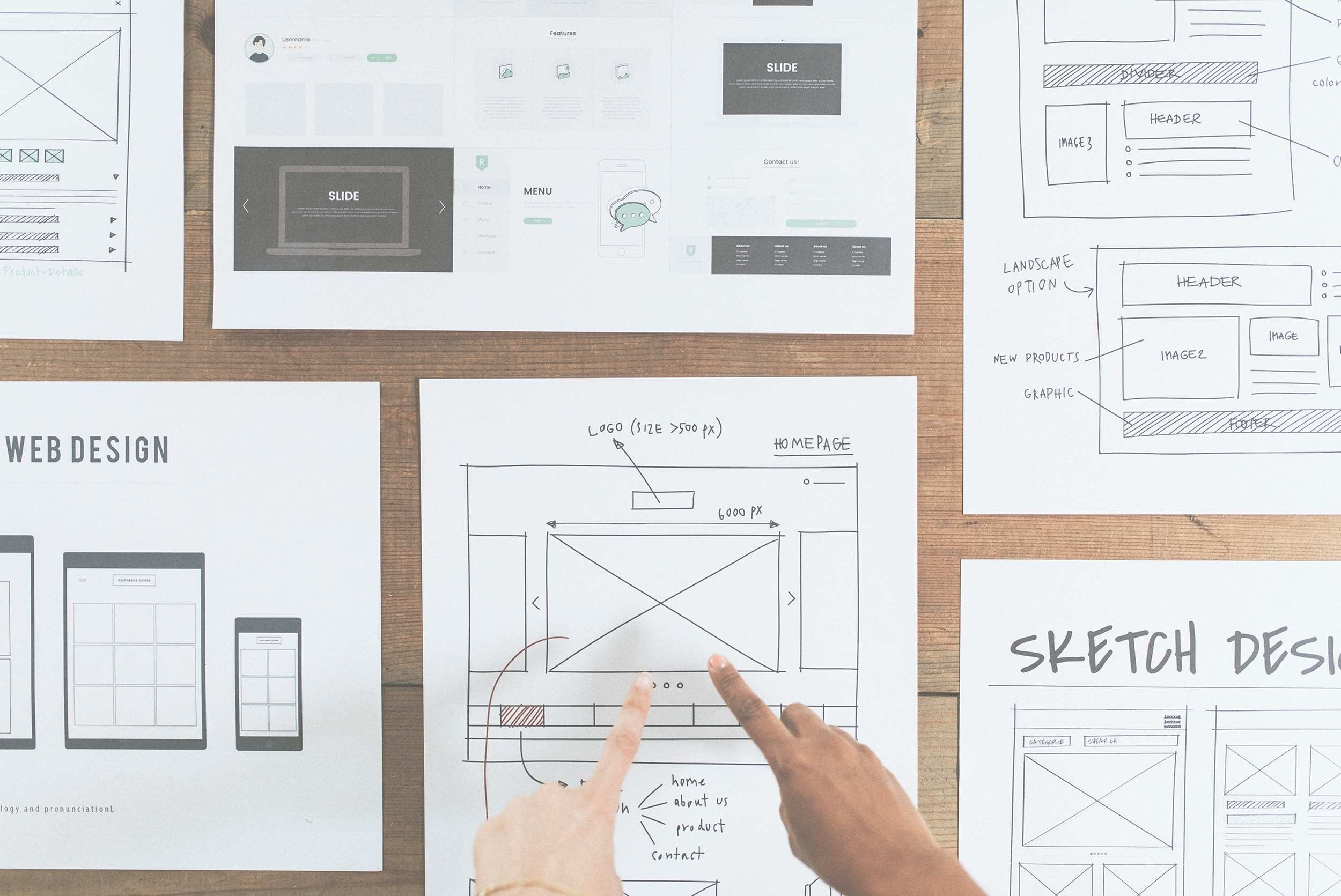 Hands point to web design document